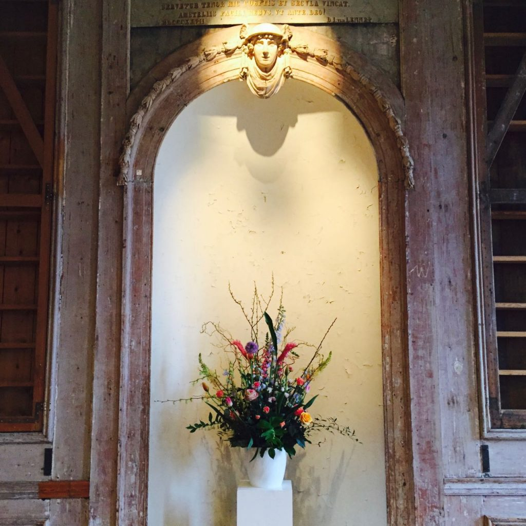 Groot bloemstuk op zuil als onderdeel van de bloemen op een evenementen locatie. Hier bij Felix Meritis