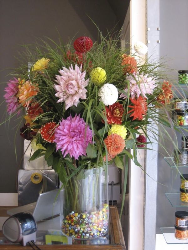 Een vaas met bloemen bij de kassa